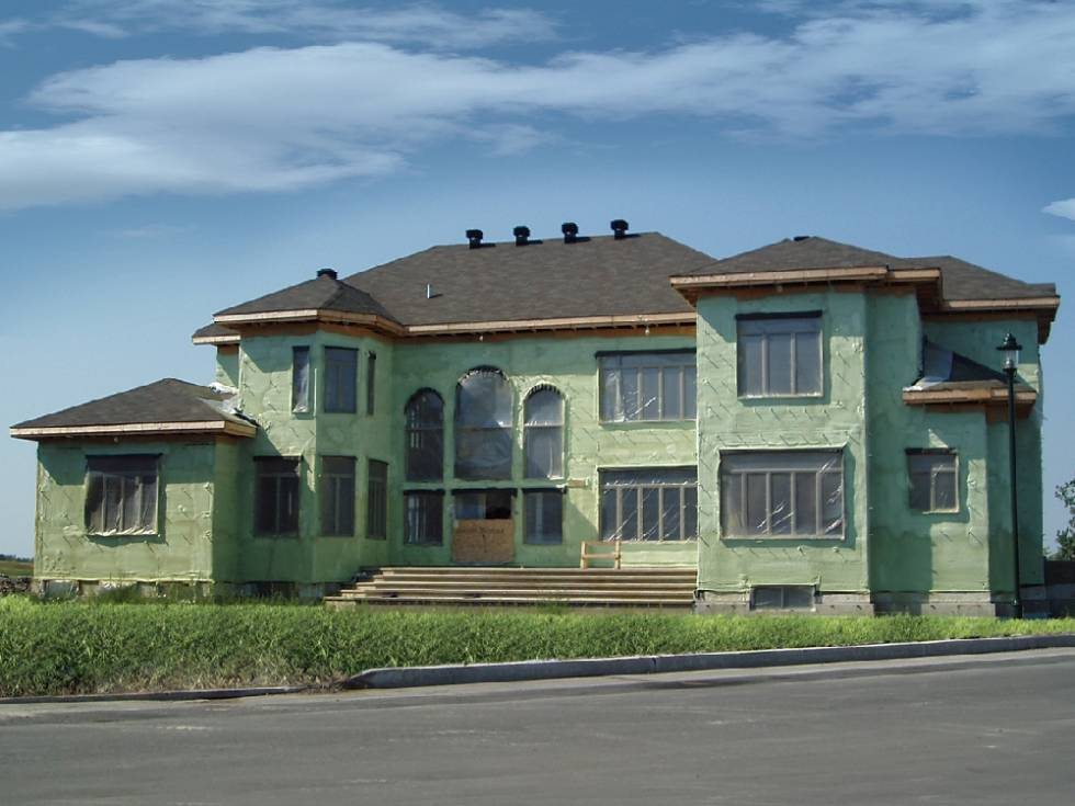 Large home in construction covered in green spray foam.